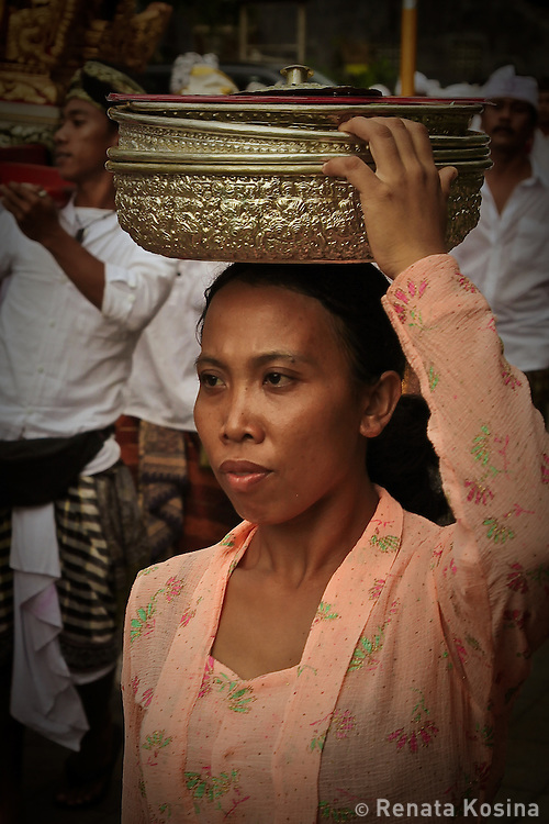 Balinese woman carries sacred temple offerings in a procession during a temple ceremony in Ubud, Bali. Such ceremonies are a way of life for the Balinese.