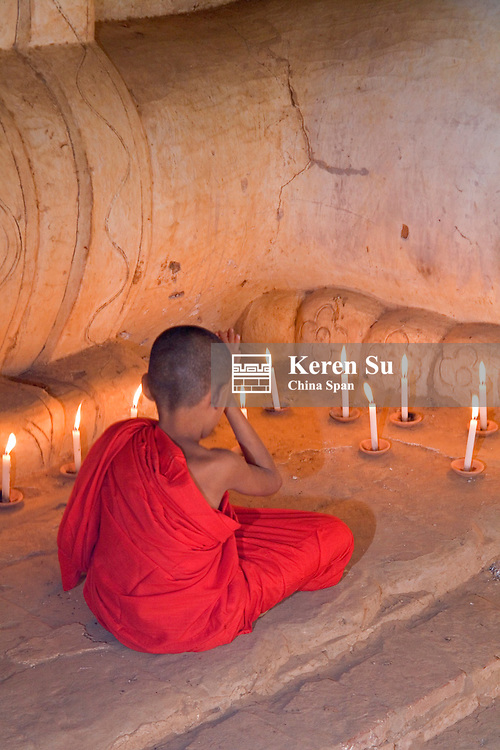 Monk praying by candles under the feet of huge Buddhist statue, Bagan, Myanmar