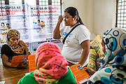 Pregnant women and lactating mothers listen to a SPRINT-IPPF reproductive health (RH) information session before receiving dignity kits at a RH Medical Mission in the Taluksangay Barangay Hall, Zamboanga, Mindanao, The Philippines on November 5, 2013. These Internally Displaced People (IDP) had taken refuge in this Barangay (neighbourhood) after surviving the 3 week long attack by MNLF rebels. Photo by Suzanne Lee for SPRINT-IPPF
