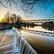 Spring at Riverside Park at dusk, walking bridge and waterfall in view.  Photo by Andrew Goodwin