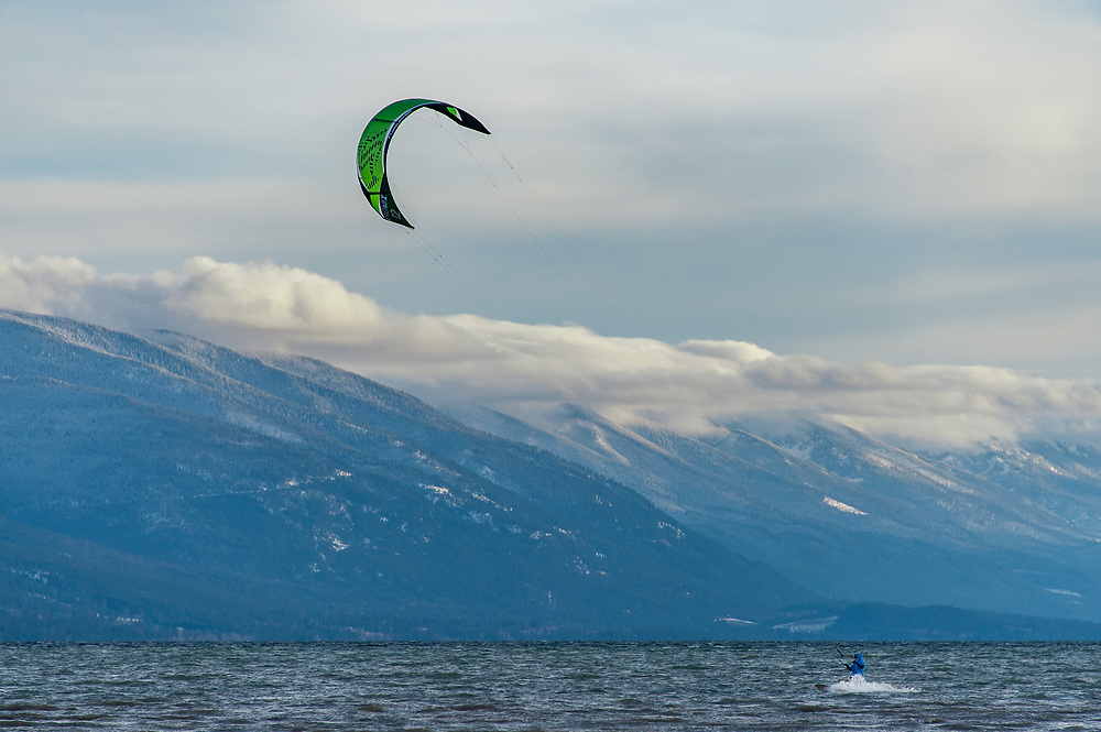 Kite surfer on Flathead Lake in NW Montana in the winter with the Mission Mountains in the background.
