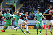 Burnley forward Ashley Barnes (10) gets a shot on goal witj Arsenal defender Shkodran Mustafi (20) Arsenal defender Stephan Lichsteiner (12) and Burnley forward Chris Wood (11) watching on during the Premier League match between Burnley and Arsenal at Turf Moor, Burnley, England on 12 May 2019.