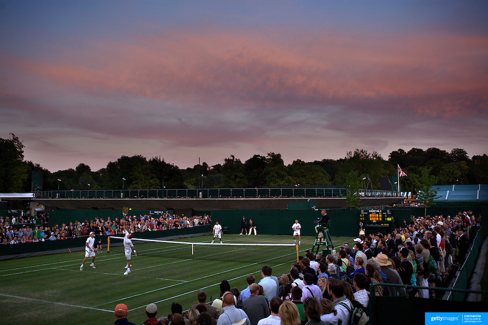 A doubles match is played out as the light drops and the sun sets  at the All England Lawn Tennis Championships at Wimbledon, London, England on Thursday, June 25, 2009. Photo Tim Clayton