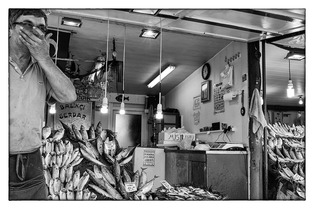 Black and White portrait of a funny sales man in a fish shop, in Sile, Turkey