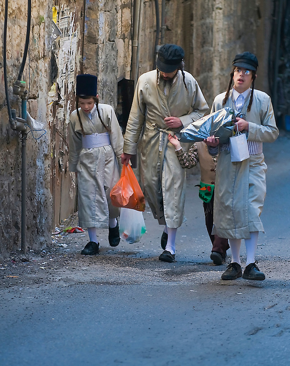 JERUSALEM - MARS 09 : Ultra Orthodox family holding Mishloac Manot during Purim in Mea Shearim Jerusalem on Mars 09 2012 , Mishloach Manot is traditional food gifts given during Purim