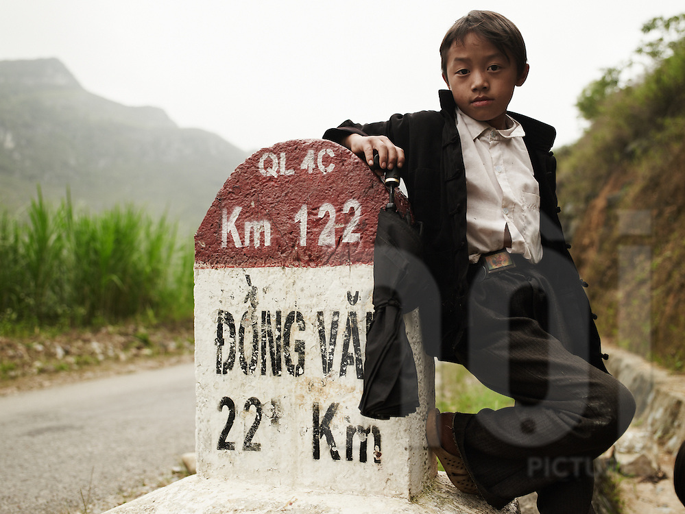 A young ethnic boy stands close a kilometer marker that indicates distance to Dong Van city. He holds a closed umbrella and looks at the camera.  Ha Giang province, Vietnam, Asia