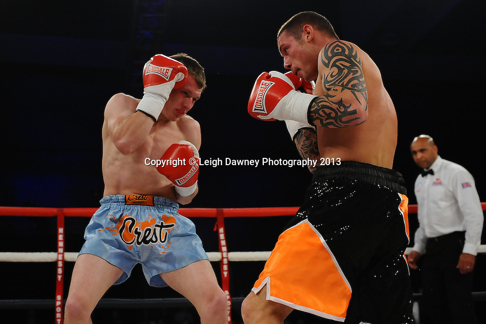 Garry Neale (black/orange shorts) boxing against Simas Volosinas in a Light Welter weight contest. Glow, Bluewater, Kent, UK. Hennessy Sports © Leigh Dawney Photography 2013.