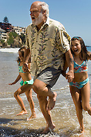 Girls and grandfather running through waves