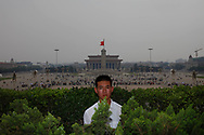A plainclothes soldiers hides in the bushes as he stands guard on a balcony ovwerlooking Tiananmen square Beijing , China, Friday, May 15, 2009. (AP Photo/ Elizabeth Dalziel)