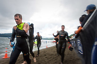 JEROME A. POLLOS/Press..Jeffrey Recker, from Grand Junction, Colo., removes his wet suit after exiting Lake Coeur d'Alene following the 2.4-mile swim  Sunday during the Ford Ironman Coeur d'Alene.