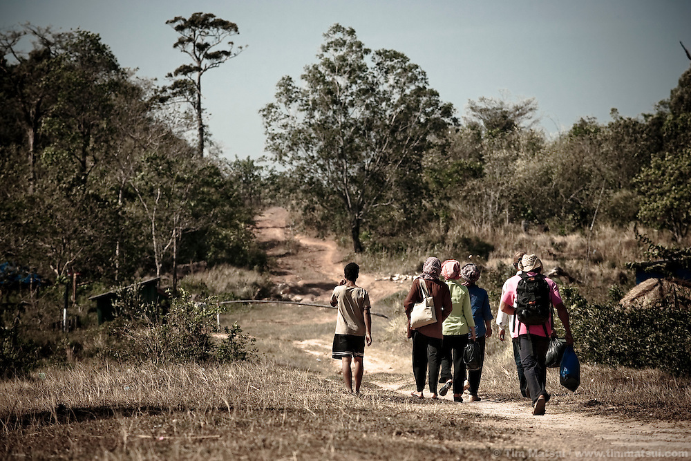 Undocumented Cambodian migrants walk with their guide, at left, towards a remote Cambodian gatehouse on their way into Thailand. NGO staff working with migrants, and the migrants themselves, say they must pay both Cambodian and Thai border guards however here, at this land mine ridden outpost, a series of clear trails weave through the thick forest enabling migrants to avoid Thai authorities.