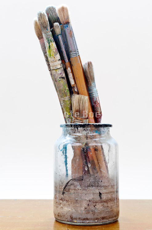 various artist paint brushes in a glass jar