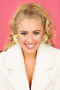 Closeup of fashion model Brenna Smith wearing pompom earrings and smiling at the camera.