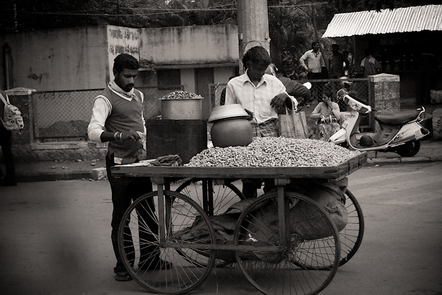 A male street vendor selling nuts to another man, whist he stops his card in the road. Mysore, Karnataka, India