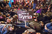 UNITED KINGDOM, London: 02 December 2015 Thousands of people gather in Parliament Square this evening as part of a Stop The War campaign. Protesters have gathered outside Parliament for a second night as they await the result of a vote on UK air strikes in Syria. <br /> Pictured: Hundreds of protesters stage a 'die-in' disrupting traffic outside Parliament in protest.<br /> Rick Findler / Story Picture Agency