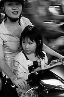 Mother and daughter sitting on a motorbike in the streets of Saigon.