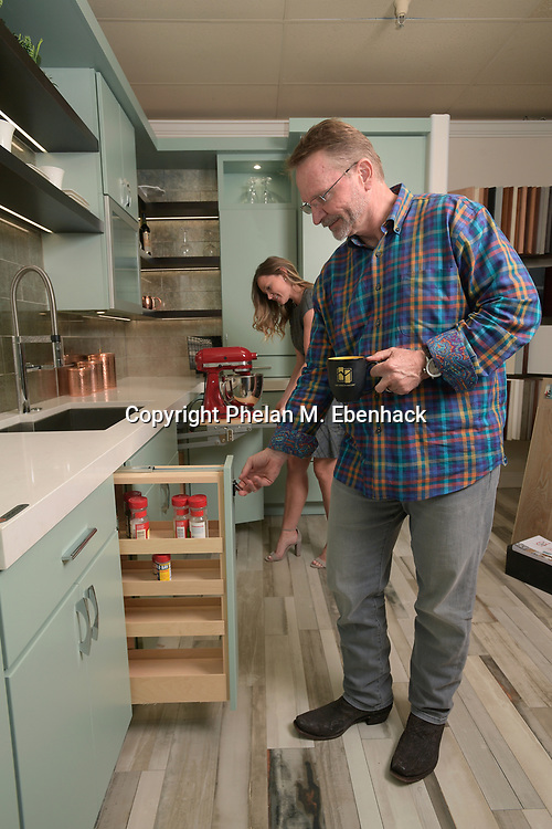 Keith Vellequette, owner and lead designer of KBF Design Gallery, left, talks with Ashley Vellequette about some of the new kitchen cabinet features in their showroom Monday, Sept. 18, 2017, in Altamonte Springs, Fla. (Photo by Phelan M. Ebenhack)