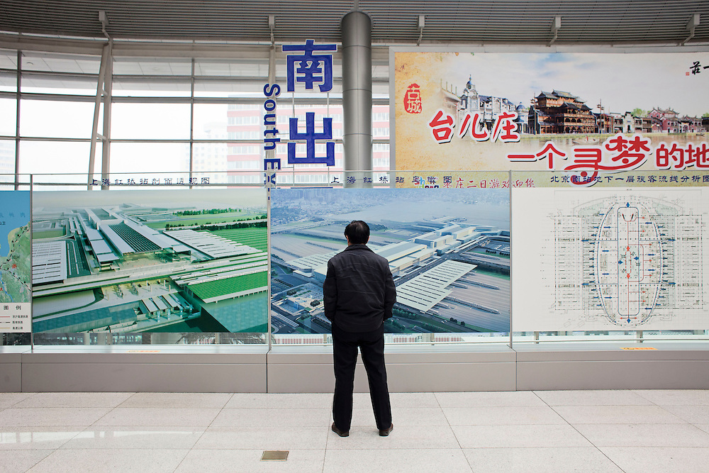 A traveller looks at photos and plans of the recetly built Beijing South Railway Station. Beijing, China. 2012