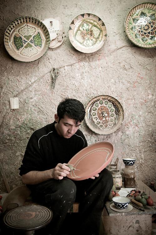 Gijduvan, Uzbekistan 22 March 2012. A ceramist works at Abdullo Narzullaev's workshop.