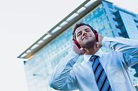 Mature businessman listening on music with headphones on