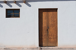 A door and window set against the stark white exterior of an abandoned house.
