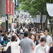Crowd of people walking along Omotesando a smart shopping street in central Tokyo. Focus is on the backgrpound of this busy urban environment.