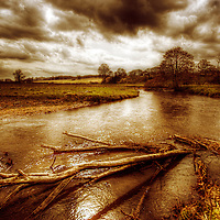 English countryside view with wide stream and debri under stormy sky