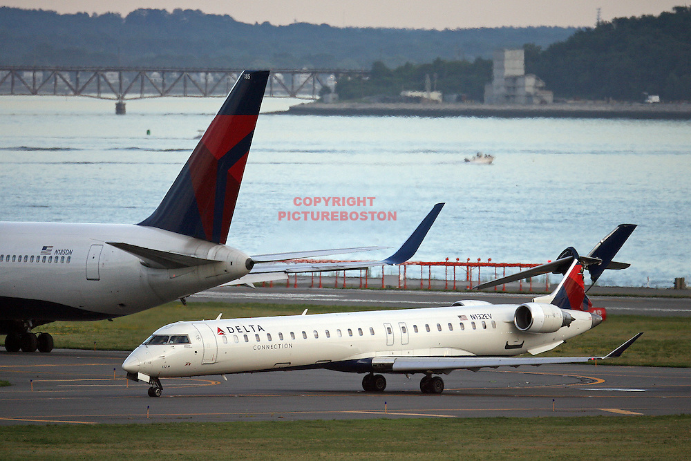 A Delta 767 airliner sits on a taxiway after it's left winglet (not shown in photo) struck a Delta Conection jet's tail (jn foreground) this evening at Logan  Staff Photo by Mark Garfinkel  .