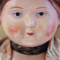 Face of vintage woman doll with tight bun and glum face and wearing lacy clothes and neckband