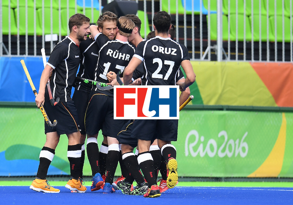 Germany's Moritz Furste (2L) celebrates scoring a goal with teammates during the men's field hockey Germany vs Ireland match of the Rio 2016 Olympics Games at the Olympic Hockey Centre in Rio de Janeiro on August, 9 2016. / AFP / MANAN VATSYAYANA        (Photo credit should read MANAN VATSYAYANA/AFP/Getty Images)