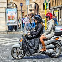 Una mujeres viajan en moto por una calle de Roma. Roma, Italia. A women travel by motorcycle in a street in Rome