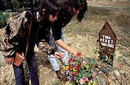 Visitors place flowers on the grave of 11-year-old Tina Pekez, who was killed in the Bosnian Serb siege of Sarajevo, September, 1992. Almost 2,000 children were killed in Sarajevo during the 3-1/2 year siege. (Photo by Roger Richards)