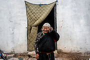 A woman stands for a portrait in front of her home in Zado, Tibet (QInghai, China)