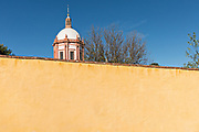 The dome of the Parroquia de San Pedro Apóstol church or Saint Paul the Apostle provincial church peaks above a colorful wall in Mineral de Pozos, Guanajuato, Mexico. The town, once a major silver mining center was abandoned and left to ruin but has slowly comeback to life as a bohemian arts community.