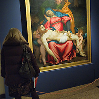 """VENICE, ITALY - NOVEMBER 23: A woman admires the """"Pieta'"""" by Lorenzo Lotto at the press preview of Tribute to Lorenzo Lotto - The Hermitage Paintings at Accademia Gallery on November 23, 2011 in Venice, Italy. The exhibition which includes two very rare & never seen before paintings opens from the 24th November 2011 to 26th February 2012 in Italy."""