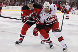 Oct 10; Newark, NJ, USA; Carolina Hurricanes right wing Chad LaRose (59) and New Jersey Devils defenseman Adam Larsson (5) battle for the puck during the first period at the Prudential Center.