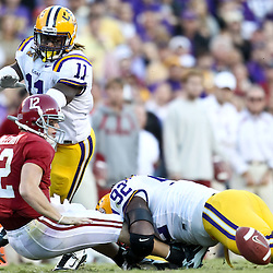 November 6, 2010; Baton Rouge, LA, USA; Alabama Crimson Tide quarterback Greg McElroy (12) fumbles as he is hit by LSU Tigers defensive tackle Drake Nevis (92) and LSU Tigers linebacker Kelvin Sheppard (11) during the second half at Tiger Stadium. LSU defeated Alabama 24-21.  Mandatory Credit: Derick E. Hingle