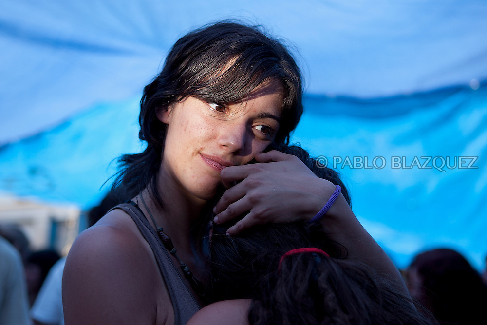 Two women embrace at the Puerta del Sol Square Camp in Madrid on June 12, 2011. Protesters installed in Madrid's Puerta del Sol square for the past month are scheduled today to dismantle their ramshackle encampment, which has become a symbol of the anti-establishment movement.