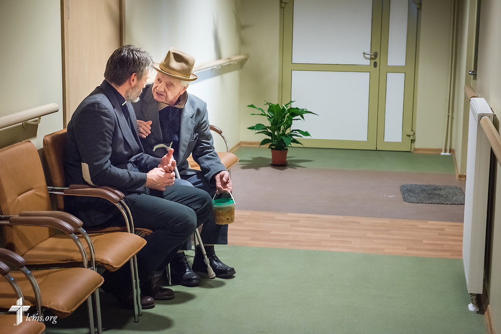 An elderly man engages the Rev. Ivo Kirsis, a parish pastor in The Evangelical Lutheran Church of Latvia, for conversation following Divine Service on Wednesday, Feb. 4, 2015, at a Diaconia Center mercy project site based at a municipal apartment in Riga, Latvia. LCMS Communications/Erik M. Lunsford