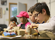 Sam Brewster, 10, of Cedar Rapids works on a carving during a meeting of the Cedar Valley Woodcarvers in Midway on Saturday, May 25, 2013.