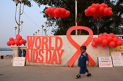 November 30, 2016 - Kolkata, West Bengal, India - An Indian children passes in front of cut outs of World AIDS Day during the awareness programme of HIV/AIDS in Kolkata, India on Wednesday, 30th November, 2016. World AIDS Day is observed on 1st December  every year to raise awareness about HIV/AIDS  (Credit Image: © Sonali Pal Chaudhury/NurPhoto via ZUMA Press)