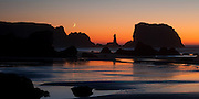 A crescent moon hangs low against the sunset over the rock formations and beach at Bandon, Oregon