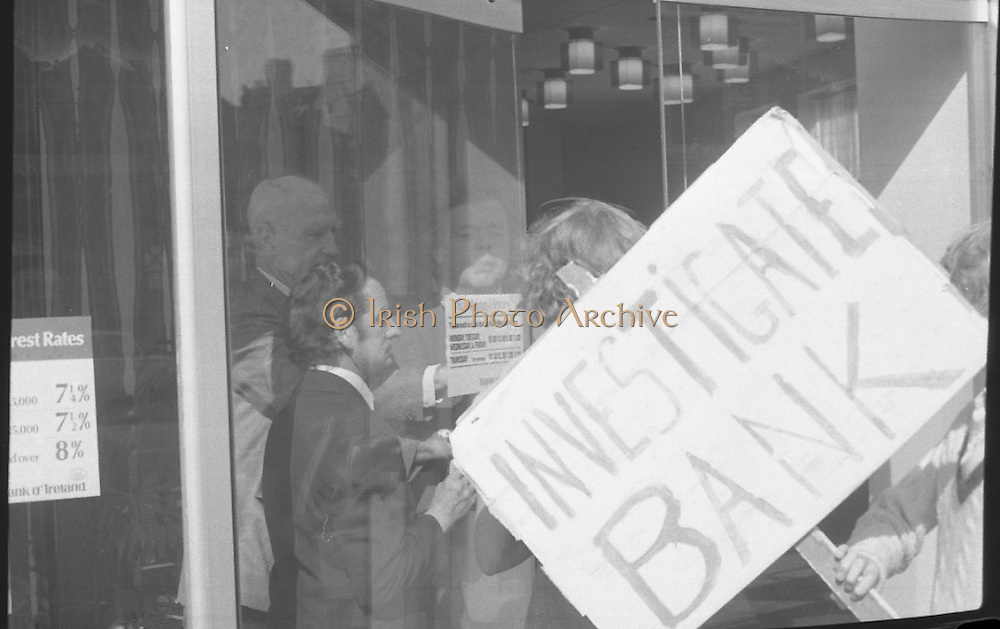 Fergus Rowan sits in at Bank of Ireland.  (J70)..1975..22.08.1975..08.22.1975..22nd August 1975..As a result of the 1970 bank strike which lasted for six months, the Rowan family business found itself in financial difficulties. During the strike the Rowans had had to accept cheques in good faith in order to stay in business. When the cheques came for settlement the bank refused as they stated that some were 'dodgy'. This put severe strain on the business which was eventually put into receivership.As part of the process the Rowan business beside the bank was put up for sale and was purchased by B.o I. Rowan was outraged and started a campaign against the bank which culminated in a sit in at the banks headquarters in Westmoreland St,Dublin. He also became a thorn in the side of the bank at the A.G.Ms raising many points...Picture of Fergus Rowan as he opens the door to allow his family and supporters to enter the bank.
