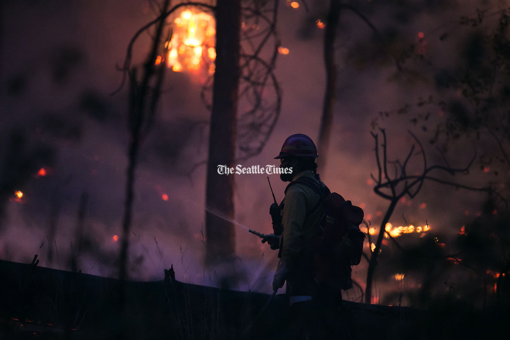 A wildland firefighter works on a blaze in Conconull on Friday August 21, 2015.<br />