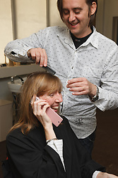 Hairdresser who has Ehlers-Danlos Syndrome (EDS), helped into employment by the Ready 4 Work team, Nottinghamshire County Council, styling a woman's hair as she talks on  her mobile phone