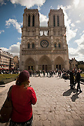 Stock  / Front view of Notre-Dame Cathedral with tourist looking on in amazement.