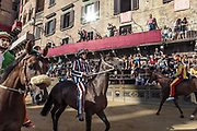"Italy, Siena, the Palio:from right , Chiocciola, Istrice , Selva.  preparing for the  trial called "" Provaccia"" , the bad trial, for the lack of enthuasiasm shown by the jockeys who spare the horses for the demanding evening race After this test, captains and jockeys gather at the City Hall to enscribe the jockey and show his colors. After this the jockey can no longer be changed."