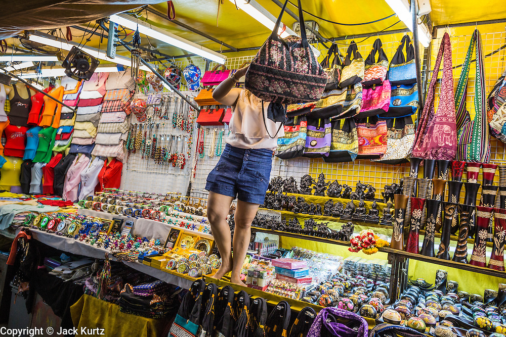 4 JUNE 2013 - BANGKOK, THAILAND:  A woman sets up her shop in the Patpong Night Bazaar in Bangkok. Patpong was one of Bangkok's notorious red light districts but has been made over as a night market selling clothes, watches and Thai handicrafts. The old sex oriented businesses still exist but the area is now better known for its night shopping.      PHOTO BY JACK KURTZ