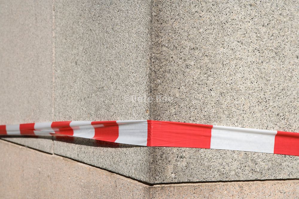 red and white protection tape placed around a big column