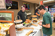 Internatinoal student Jiono Hu (Right) enjoys a complimentary Thanksgiving lunch from the College of Health Sciences and Professions at the Atrium Cafe in Grover Center. Photo by Ben Siegel